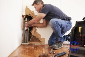 An Emergency Plumber Fixes a Pipe Behind the Wall