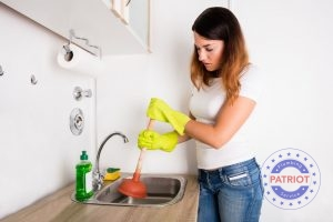 Young Woman Frustrated with Plunging the Kitchen Sink