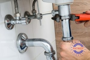Plumber Adjusts Fittings Under Bathroom Sink