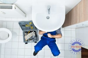 A Plumber Fixes Pipe Fittings Beneath a Sink
